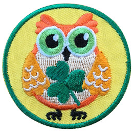 This orange owl holds a three-leaf clover in its wings.