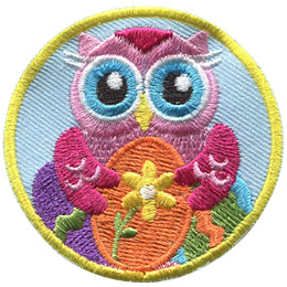 A pink owl holds a painted Easter egg decorated by a flower. Two other painted eggs sit in the background of this round crest.