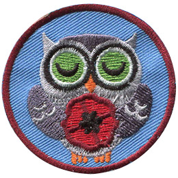 <p>This circluar patch displays an grey owl with his eyes closed and his wings holding a poppy.</p>