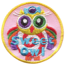 This owl is covered in sweets and a rainbow of colours. On it\'s head is a purple wrapped candy. It\'s belly consists of a red and white swirl. The owl\'s wings are rainbow and it has one purple eye and one green eye.
