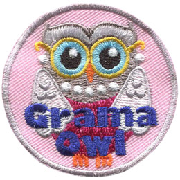 An elderly owl is attired in a pink dress, gold-rimmed glasses, pearl earnings, and a pearl necklace. This owl\'s white wings look like a shall draped over the shoulders. The words \'Grama Owl\' are embroidered near the bottom of this round crest.
