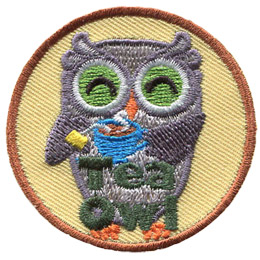A grey owl smiles and holds a steaming cup of tea with the tea bag still in it. At the bottom of this crest are the words 'Tea Owl'.