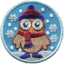 A brown owl stares wide-eyed ahead. It is dressed in a warm toque, scarf, and boots as it stands amongst falling snowflakes.