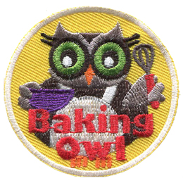 An owl stands in a white cooking apron and holds a bowl in its left wing and whisk in its right. The words Baking Owl rest at the bottom center of the crest.