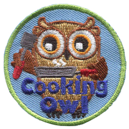 A brown owl stands holding a spatula in its left wing and steaming frying pan in its right. The words Cooking Owl rest at the bottom center of the crest.
