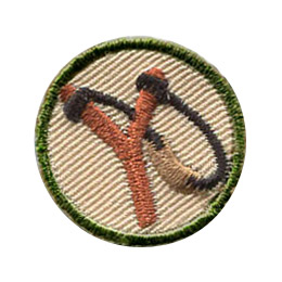 This circular, 1 inch patch depicts a slingshot. A wooden stick in the shape of a Y has an elastic string tied to the tip of each Y-branch. The string connects to a leather strap in the middle.