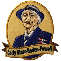 This patch displays a portrait of Lady Olave Baden-Powell wearing a blue and white hat and a blue blazer.
