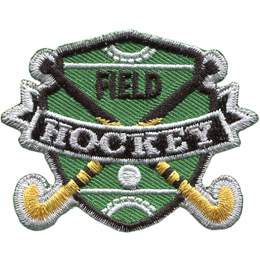 A shield shaped background showcases a green hockey field with the word 'Field'. Two crossed sticks and a ball overlay the field. A banner displaying the words 'Hockey' is situated over top where the sticks overlap.