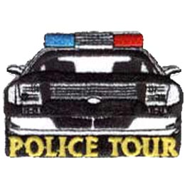 A black and white police car drives towards the viewer with the words ''Police Tour'' embroidered in gold underneath.