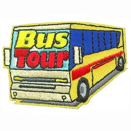 A yellow tour bus with blue tinted windows drives towards you. The words ''Bus Tour'' are embroidered on the front windshield.
