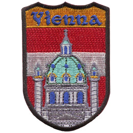 This emblem has the name \'Vienna\' at the top on a orange background. Just below it is the red and white of Vienna\'s flag. Front and center is the church of Rektoratskirche St. Karl Borromaus, commonly called Karlskirche.