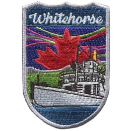 This shield shaped crest showcases Whitehorse. The ship 'Klondike' sits on the water before green fields and mountains. A Canadian maple leaf rises up in the background amidst the northern lights. The text 'Whitehorse' is at the top.