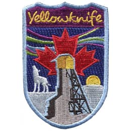 This shield shaped crest showcases Yellowknife. The a wolf howls at the sky on a snowy field as the sun sinks below the horizon. A Canadian maple leaf rises up in the background amidst the northern lights. The text \'Yellowknife\' is at the top.