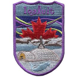 This shield shaped crest showcases Iqaluit. St. Jude\'s Cathedral stands at the forefront with Frobisher Bay and the mountains in the background. A Canadian maple leaf rises up in the background amidst the northern lights. The text \'Iqaluit\' is at the top.
