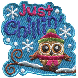 A little owl is bundled up in a toque and scarf as it sits on a snow covered tree branch. Snowflakes fall from the sky accompanied by the text 'Just Chillin'.