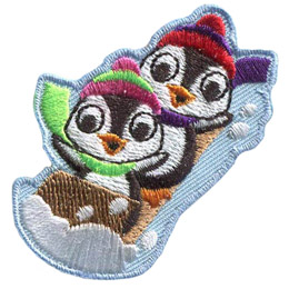 Two penguins raise their flippers in the air as they speed along on a wooden toboggan. The penguins are wearing toques and scarves.
