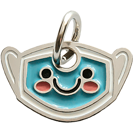 This metal charm is shaped like a medical mask. On it's face are two round eyes, a U-shaped mouth, and blushing cheeks.
