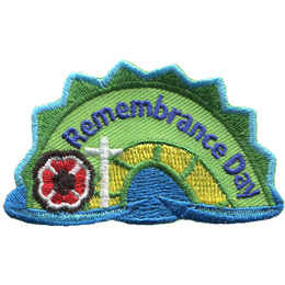 The middle hump of a sea serpent. The words 'Remembrance Day' are embroidered along the middle of the hump. A poppy and a cross rest on the left most section of the hump.