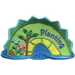 The middle hump of a sea serpent. The word \'Planting\' is embroidered along the right of the hump. A handful of seeds, two flowers, and a sapling rest on the left most section of the hump.