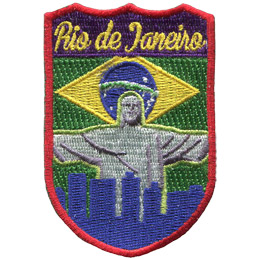 This emblem has the name \'Rio de Janeiro\' at the top on a purple background. Just below it is the green, yellow and blue of Rio\'s flag. Front and center is the statue of Christ the Redeemer with his arms outstretched over the skyline of Rio.
